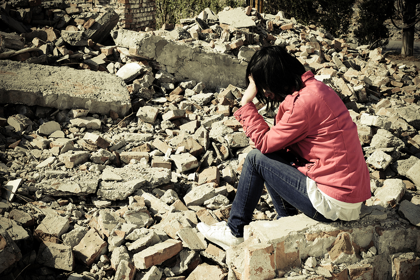 woman sitting in rubble