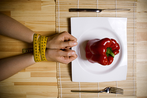 hands bound by measuring tape and red pepper on a plate